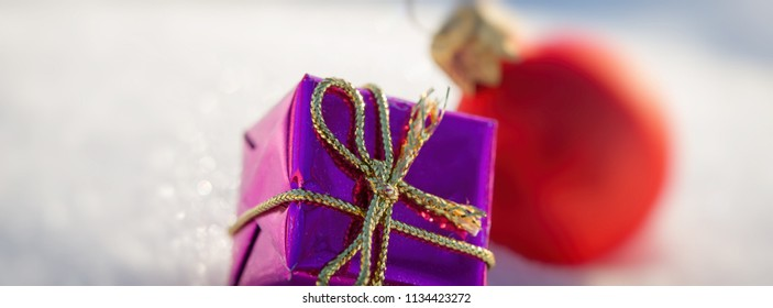 Greeting card. Christmas purple box and red ball on snow. Long banner format.