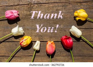 Greeting card with colorful Tulips on wooden table with words Thank you