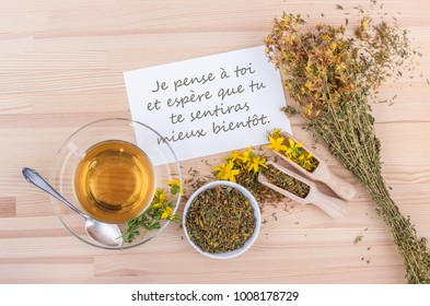 Greeting card with a cup of tea with dried and fresh St. John's wort and white card with french text: I hope you make a swift and speedy recovery