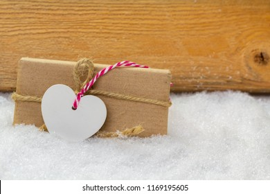 Greeting card, gift with heart in the snow