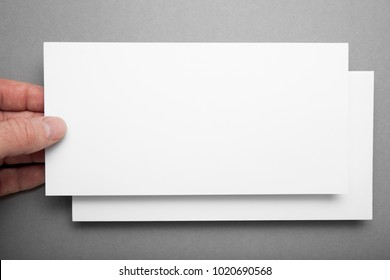 Greeting card in hand on gray background, mock up.
