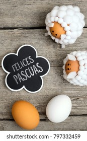 Greeting card with lamb figures and eggs on wooden table, spanish text felices pasquas, which means happy easter