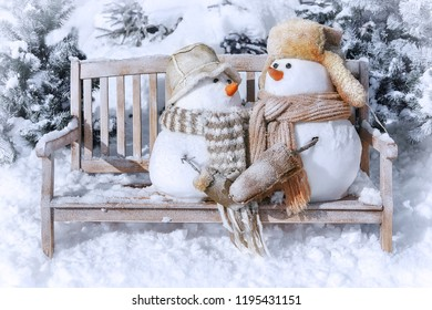 Greeting card Merry Christmas and Happy New Year with cute snowmen on a bench against the background of a winter landscape