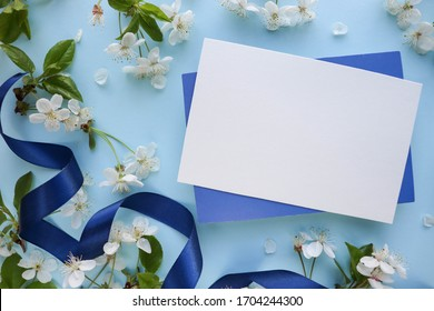 greeting card mockup. flowering cherry branch and envelope on a blue background. congratulation. invitation. place for text. flat lay