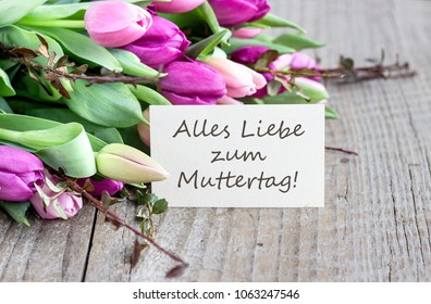 Greeting card to Mother's Day with pink and violet tulips, heart and german text: Happy Mother's Day