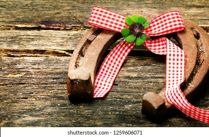 Greeting card New Year, horseshoe and four-leafed clover on wood