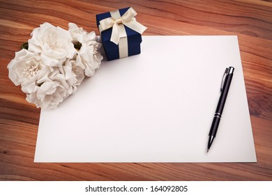 Greeting card with pen, white flowers and a blue gift box