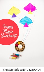 Greeting Card saying Happy Makar Sankranti with Til Gul OR Sweet Sesame Laddu, Miniature Fikri and Kite model with haldi Kumkum and sugar crystals over moody background