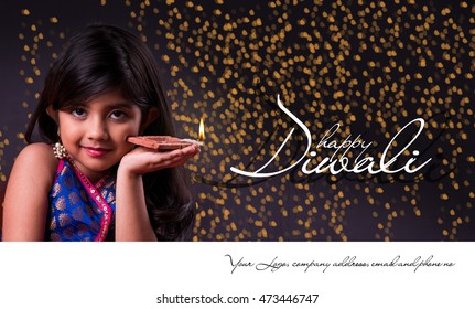 Greeting card showing Cute little indian/asian girl in traditional wear holding a diya or Terracotta oil lamp on Diwali festival. Front view over black background