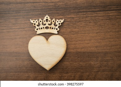 Greeting card with wooden heart on wood table background. Concept for Valentines Day or king , queen power.