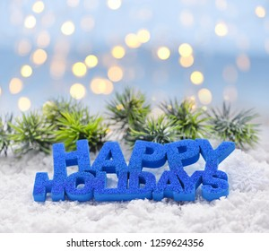"""Greeting """"Happy Holidays"""" on snow against the background of festive lights. Christmas or New Year greeting card."""