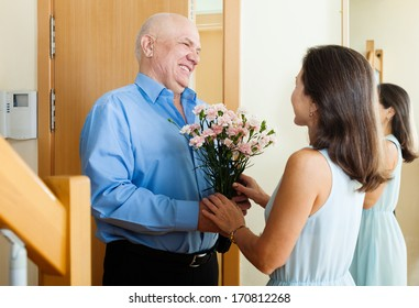 Greeting of loving mature couple at home door