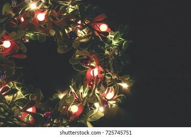 Greeting Season concept.Christmas wreath with decorative light on dark wood background