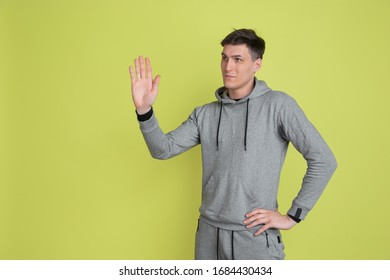 Greeting somebody. Caucasian man's portrait isolated on yellow studio background. Freaky male model in casual clothes. Concept of human emotions, facial expression, sales, ad. Unusual appearance.