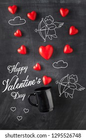 Greeting written on blackboard for Valentine's day with heart shape candy and amour cupid baby