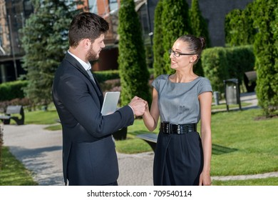 Greetings from new business partner. Businessman shaking hands with businesswoman.