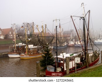 Greetsiel, Germany - November 25, 2016: Typical fishing boats moored in the harbor during a misty day