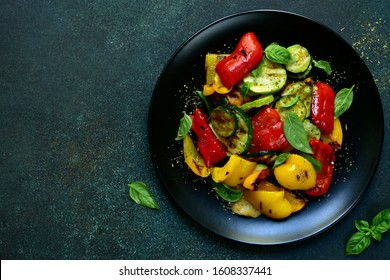 Grelled vegetables with fresh basil on a black plate on a dark green slate, stone or concrete background. Top view with copy space.