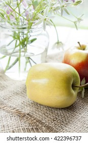 Gren and red apples in jar and white flowers on table