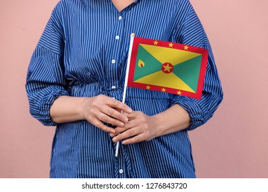 Grenada flag. Close up picture of hands holding national flag of Grenada.