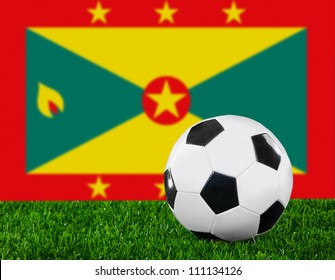The Grenada flag and soccer ball on the green grass