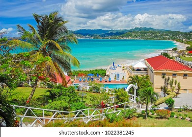 GRENADA ISLAND - MAR 7, 2009: View of Grand Anse beach and luxury hotel from tropical garden on sunny beautiful day. This island is a sovereign state in the southeastern Caribbean Sea.