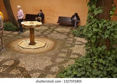 GRENADA, SPAIN - NOV 23, 2018 - Arabic style  interior garden  with fountain in the Alhambra Palace, Grenada, Spain