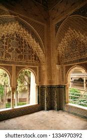 GRENADA, SPAIN - NOV 23, 2018 - Arabic windows look out on interior garden  in the Alhambra Palace, Grenada, Spain