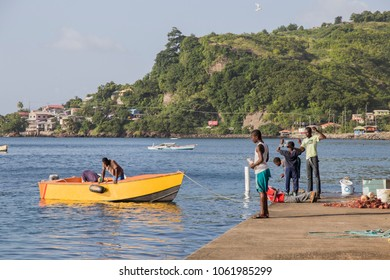 GRENADA-ANTILLES: Children Fishing at the harbor in St George Grenada on Dec 6, 2017