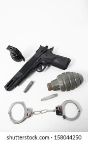 Grenade Bullets Gun and Handcuffs on a White Background