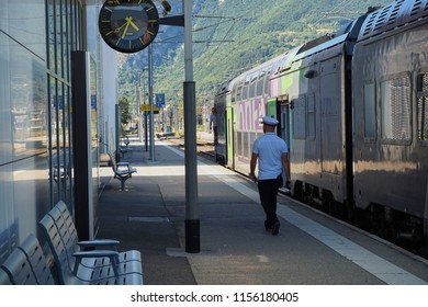 GRENOBLE, FRANCE - AUGUST 10, 2018: people taking the train, train starting with a controller