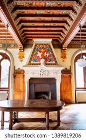 GRESSONEY SAINT JEAN - AOSTA VALLEY - ITALY - APRIL 22, 2019: Savoia Castle inside. Lunchroom; fireplace with the coat of arms of the Savoys and the Fert and Sabaudio Node emblems.  Aosta, Italy.