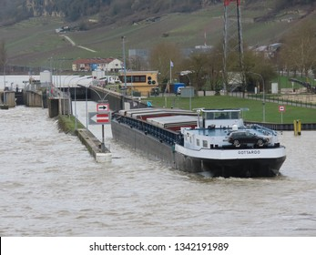 Grevenmacher / Luxembourg 03/16/2019:  River cargo boat entering lock on Moselle river on a spring day with high water