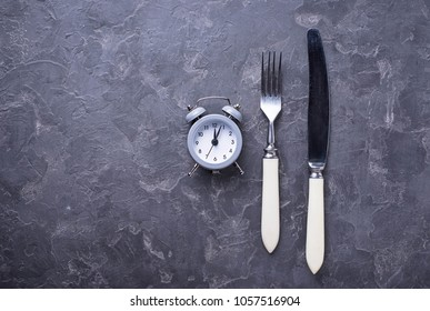 Grey alarm clock with knife and fork. Top view