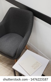 Grey armchair and minimalistic table white and black with metal construction.Book on table with sample of text.Concept.