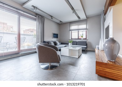 Grey armchair next to white table in modern living room interior with vase on cupboard and windows