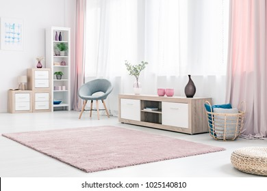 Grey armchair next to a wooden cupboard with dark vase in spacious, pink living room interior