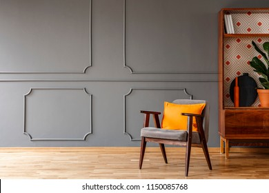 Grey armchair with orange pillow standing in real photo of dark grey living room interior with wainscoting on the wall and empty space for your coffee table