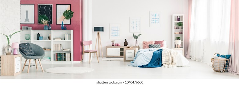 Grey armchair and pink wall in spacious bedroom interior with blue blanket on bed next to a wooden lamp