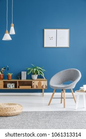 Grey armchair and pouf in living room interior with wooden cupboard against blue wall with posters
