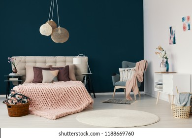 Grey armchair with powder pink blanket and cushion standing in the corner of white and blue bedroom interior with king-size bed with handmade coverlet and many pillows
