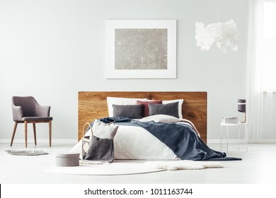 Grey armchair standing next to wooden bedhead bed with pillows in bright bedroom interior with silver poster on the wall
