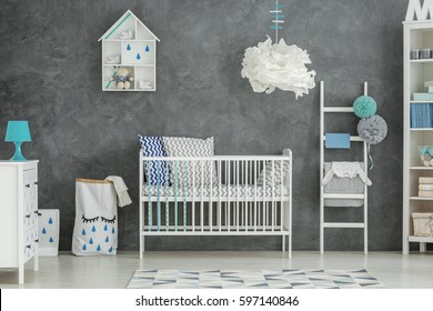 Grey baby bedroom with white cot and dresser