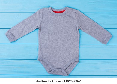 Grey baby pajama onesie creeper. Blue wood background.