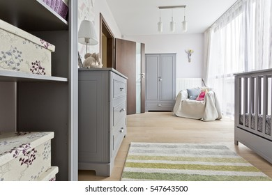Grey baby room with elegant baby cot, commode, wadrobe and panoramic windows