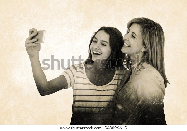Grey background against cheerful mother and daughter taking selfie