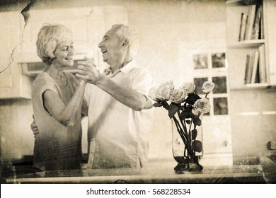 Grey background against cheerful retired couple dancing