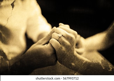 Grey background against couple holding hands with engagement ring