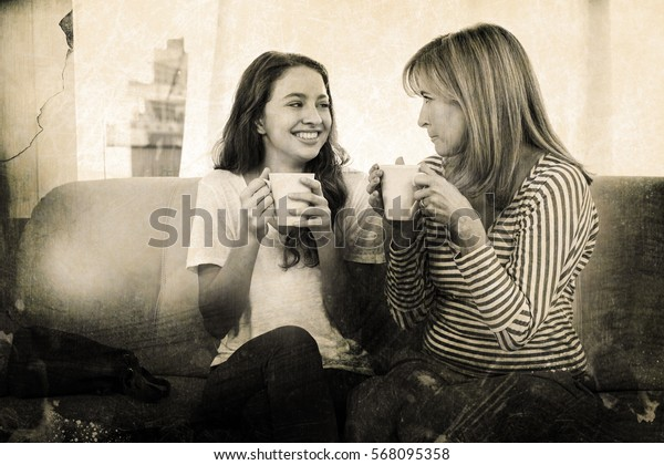 Grey background against mother and daughter drinking tea