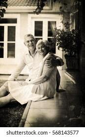 Grey background against portrait of senior couple sitting in yard